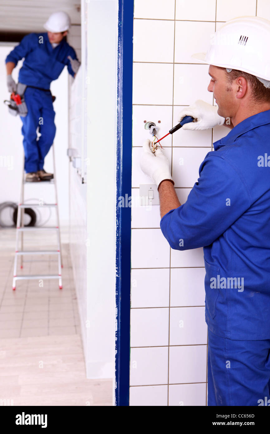 an electrician screwing an electrical outlet and a colleague on a stepladder - Stock Image