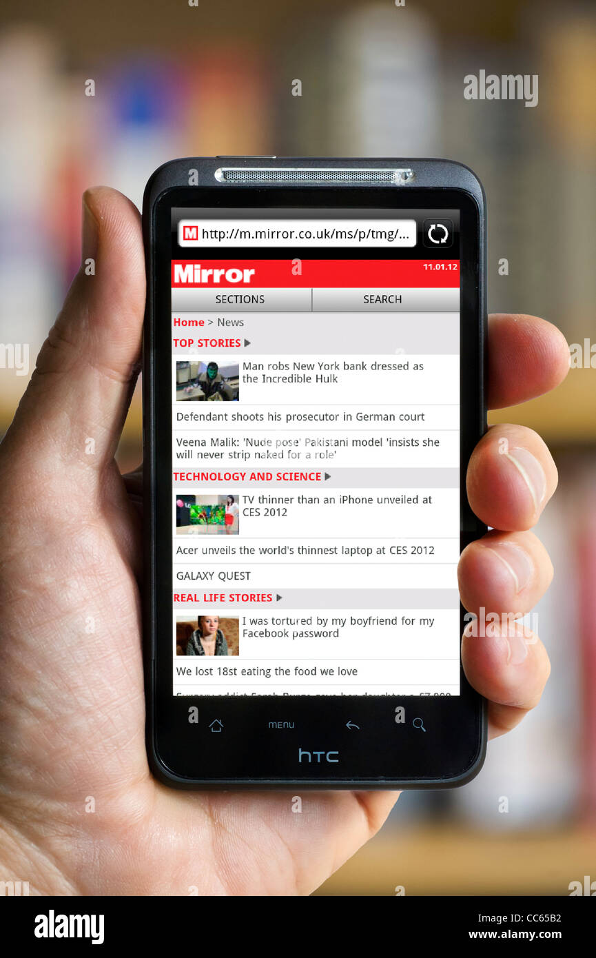 Browsing The Mirror online newspaper site on an HTC smartphone - Stock Image