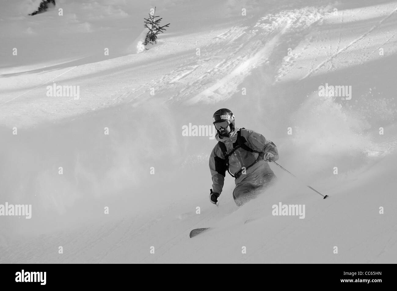 A skier turns in deep powder snow, off piste in the ski resort of Courchevel in France on Christmas Day. - Stock Image