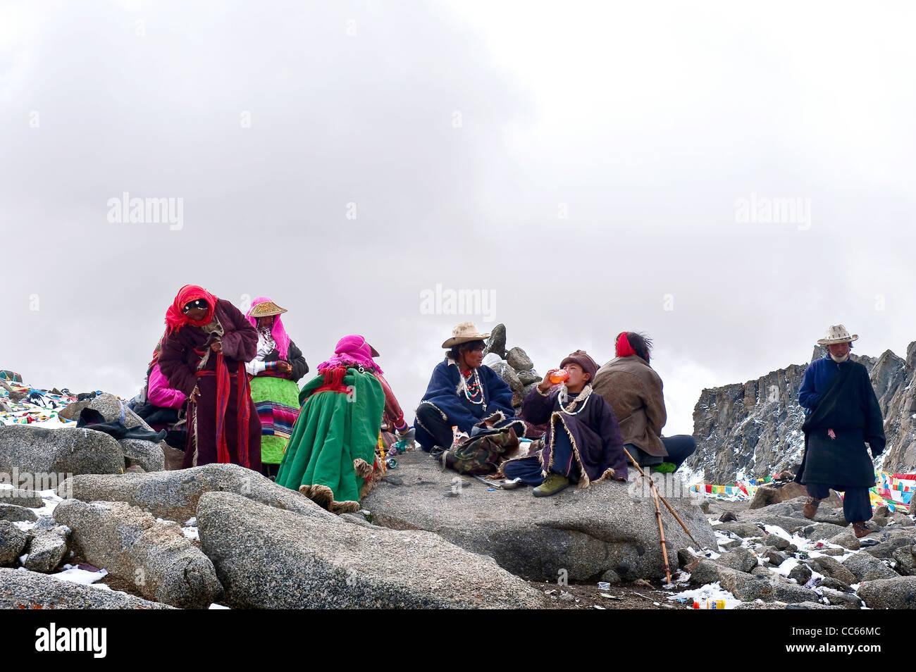 Tibetan people resting on a mountainside, Ngari, Tibet, China - Stock Image
