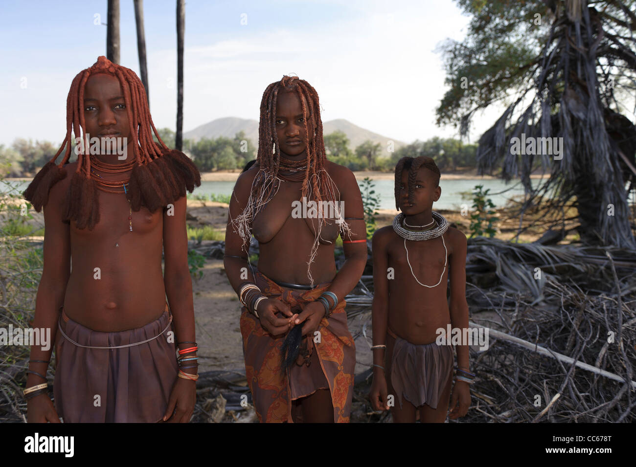 Himba girls near the Kunene River, the border between Angola and Namibia. Kaokoland, Northern Namibia. - Stock Image