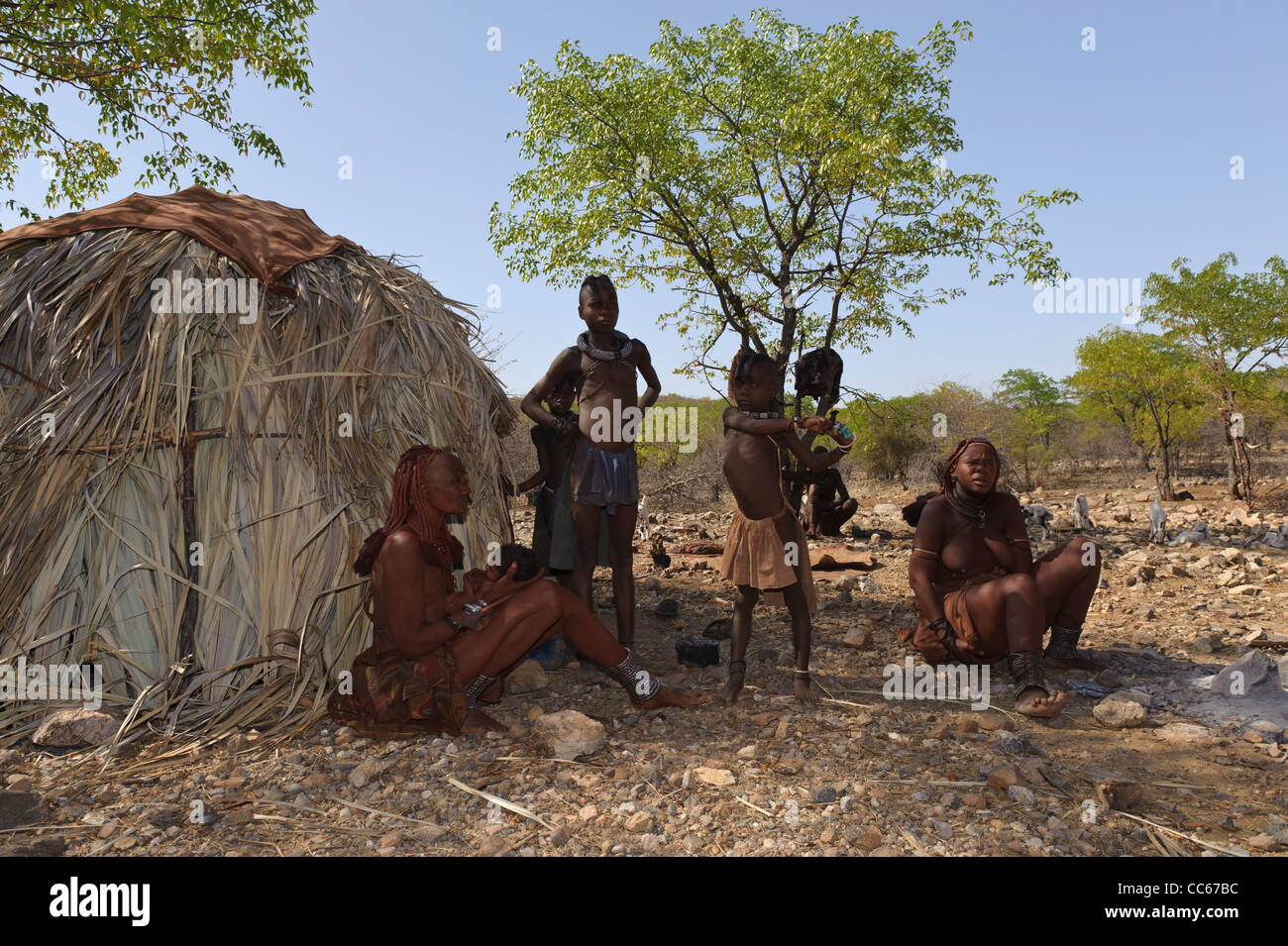 Himba villagers near the Kunene River, the border between Angola and Namibia. Kaokoland, Northern Namibia. - Stock Image
