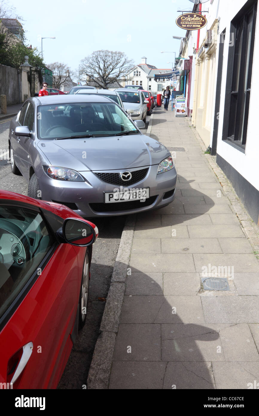Car badly parked on pavement in Rostrevor, County Down, Northern Ireland - Stock Image