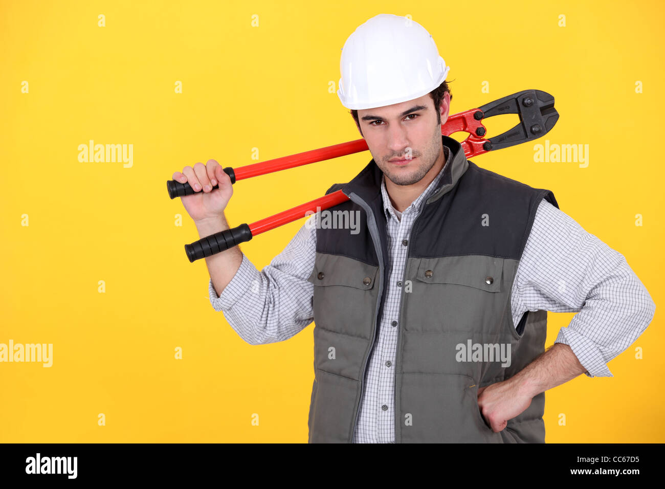 Tradesman carrying a pair of large clippers on his shoulder Stock Photo