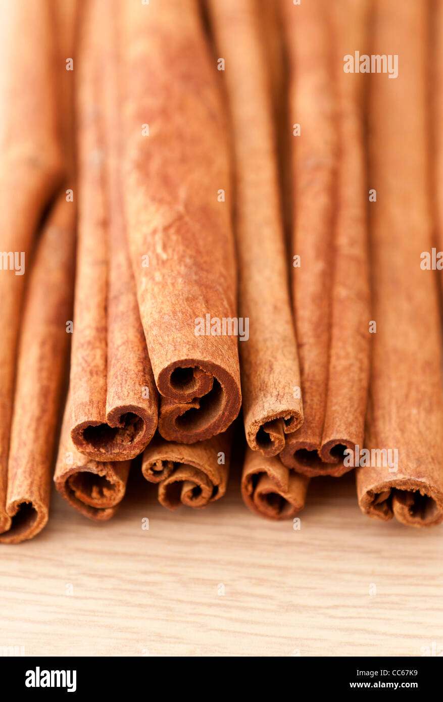 Cinnamon sticks on a wooden table top surface - Stock Image