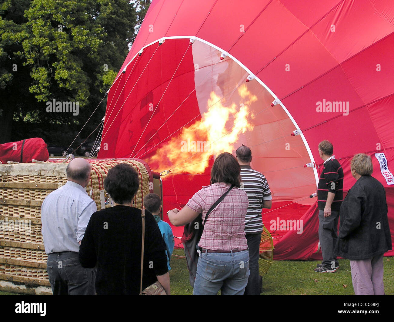 Firing the propane burners during final inflation of a hot air balloon, Royal Victoria Park, Bath, England. - Stock Image
