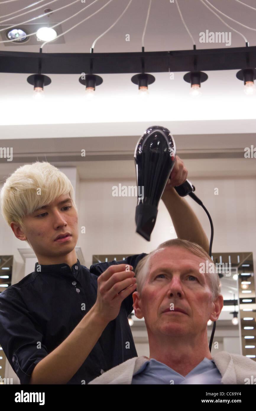 hairdresser blow drying customer's hair, Centro Salon, Suria KLCC mall, Kuala Lumpur, Malaysia - Stock Image
