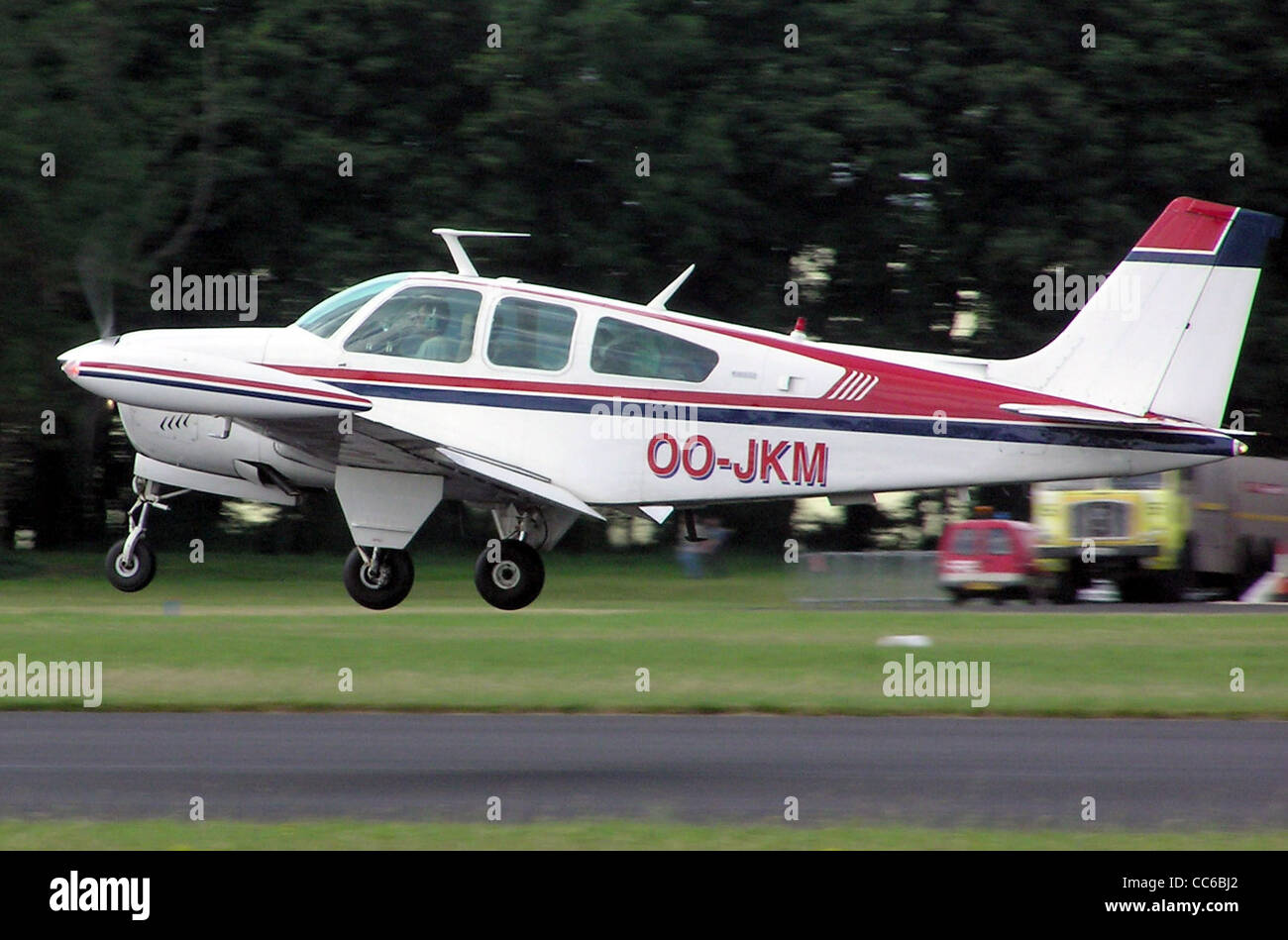Beechcraft Bonanza Be33 (Belgian registration OO-JKM) taking off at Kemble Airfield, Gloucestershire, England - Stock Image