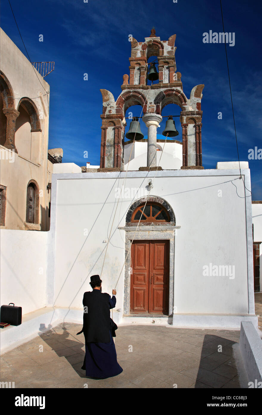 A Greek Orthodox priest tolling the bells of a church in picturesque Pyrgos village, Santorini island, Cyclades, - Stock Image