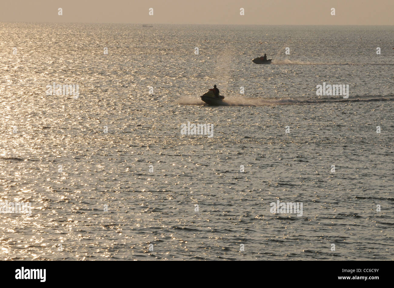 People driving yatch on South China Sea at sunset, Beihai, Guangxi , China - Stock Image