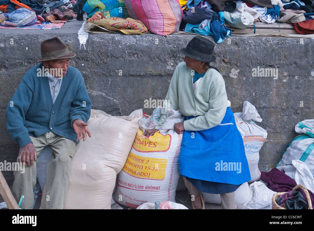 An elderly man and wife of Andean Indian descent sit on sacks of grain in the famous market town of Saquisili, Ecuador. - Stock Image