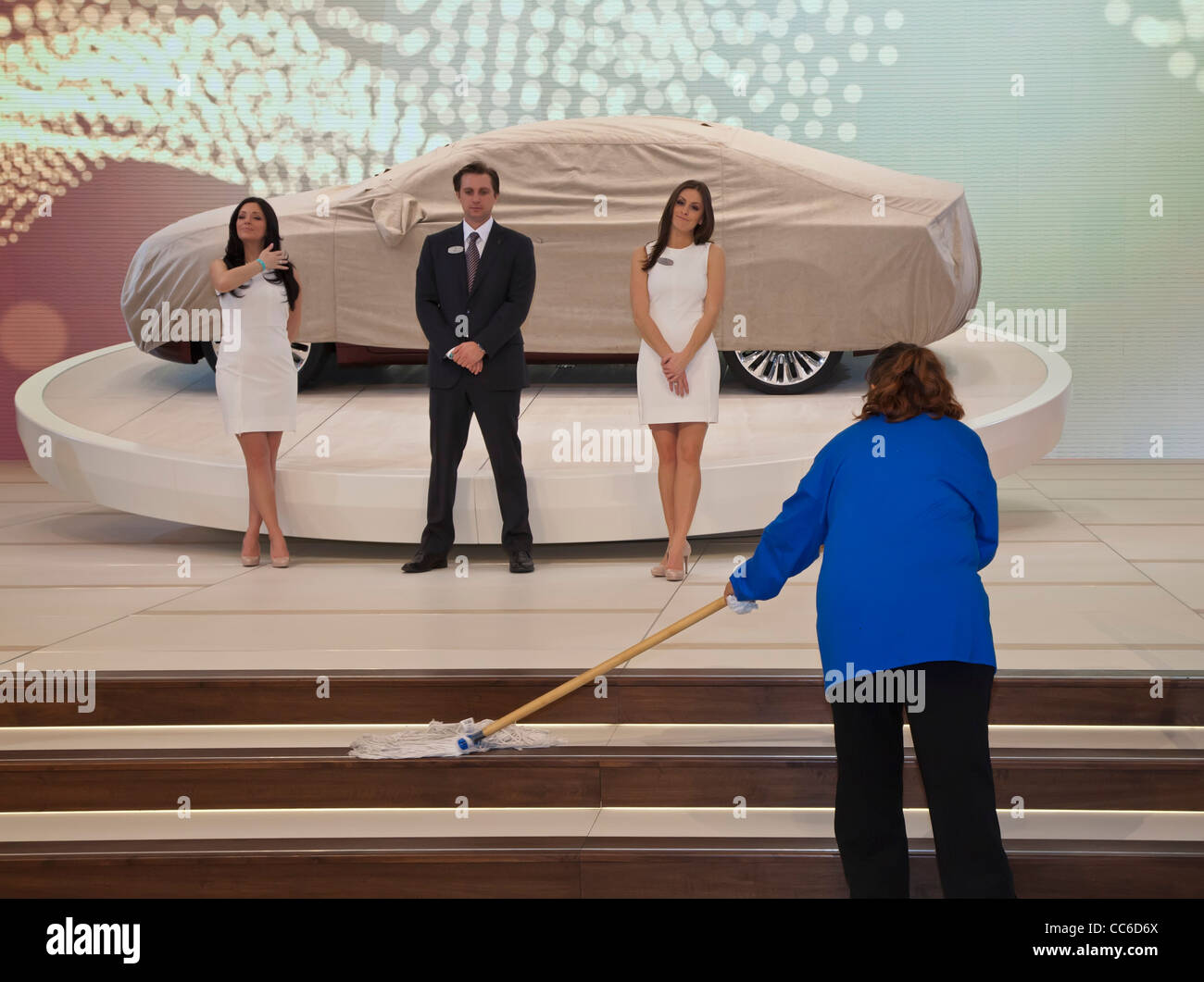 Janitor and Models at Auto Show - Stock Image