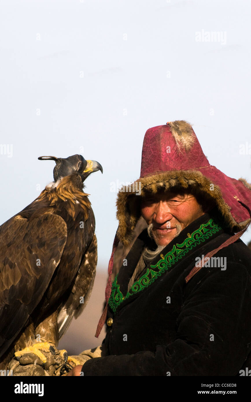 An old Kazakh eagle hunter with his Golden eagle. Stock Photo