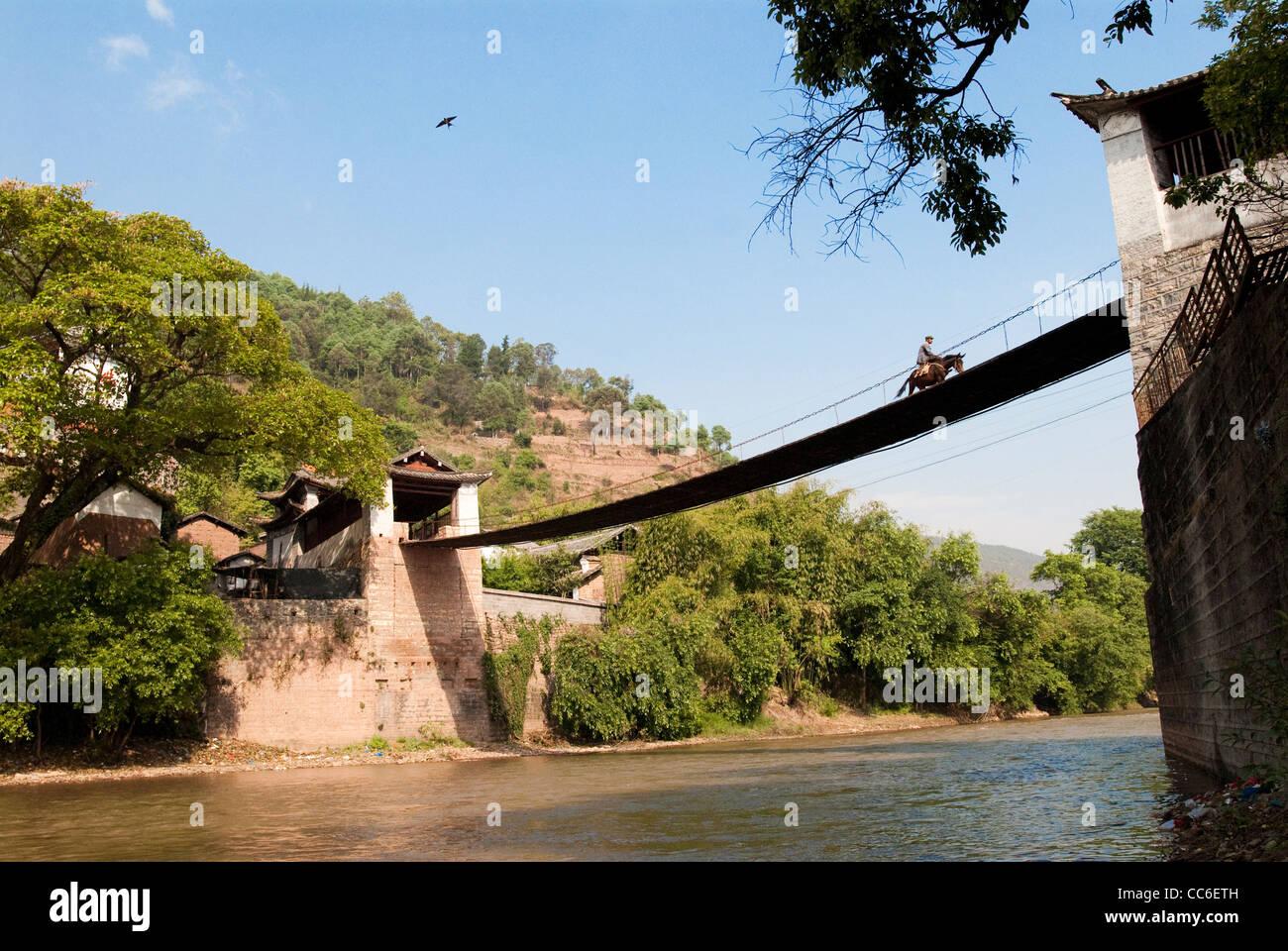 Man riding horse on the Yunlong Bridge, Dali, Yunnan , China - Stock Image