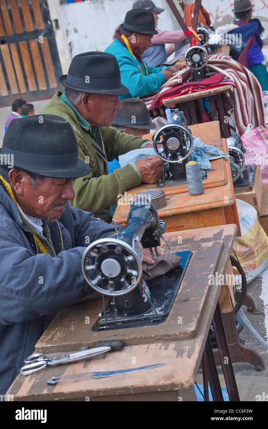 Four older Ecuadorian men sew on old fashioned pedal sewing machines outside in the famous market at Saquisili, - Stock Image