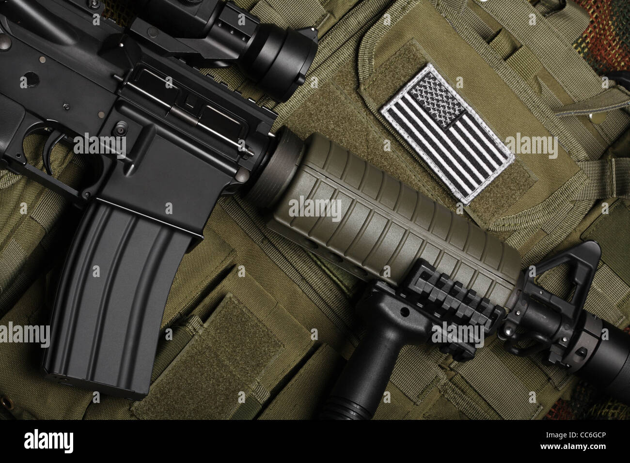 Military concept, still life. Tactical vest with U.S. battle flag and assault rifle close-up. - Stock Image