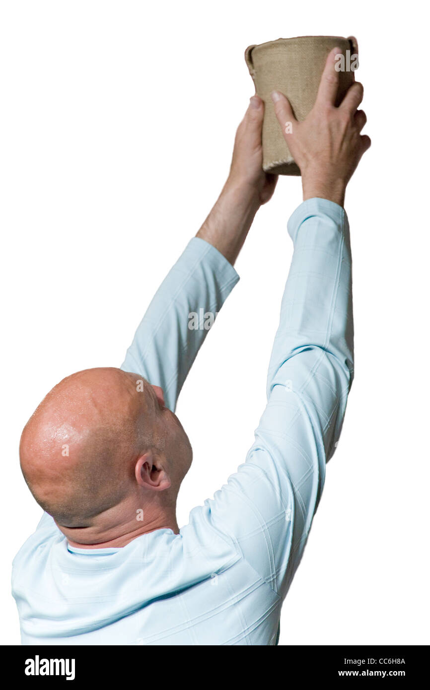 White bald man holds up begging pot with arms outstretched - Stock Image