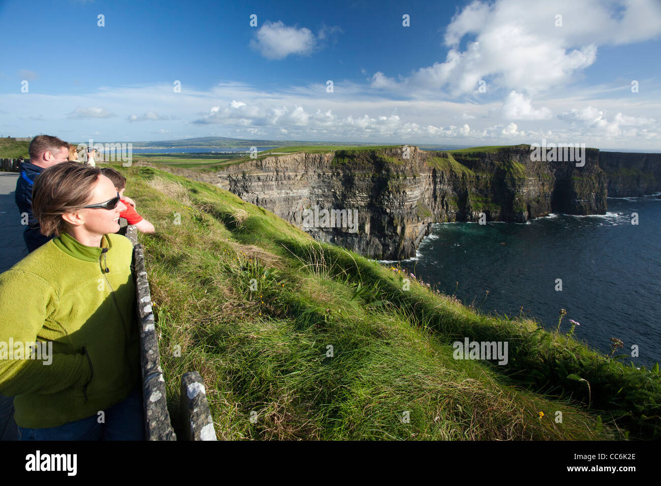 Tourists enjoying the view at the Cliffs of Moher, The Burren, County Clare, Ireland. - Stock Image