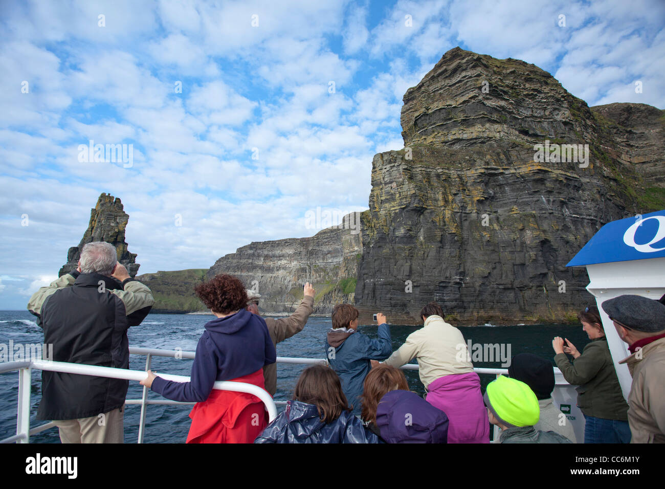 Tourists admiring the Cliffs of Moher from a scenic boat tour, County Clare, Ireland. - Stock Image