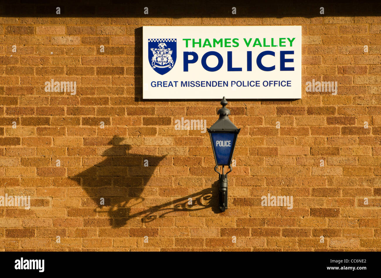 Thames valley police sign and carriage lamp on the side of a brick wall in Great Missenden Bucks UK - Stock Image