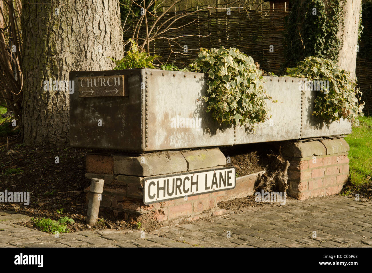 A galvanised metal horse trough now used as a container for growing plants and flowers in Church lane Great Missenden - Stock Image
