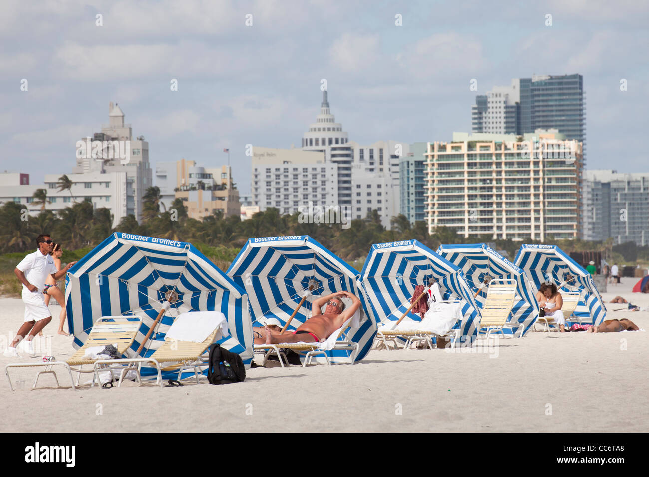 tourists with sunshade at the beach with the South Beach Skyline, Miami, Florida, USA - Stock Image