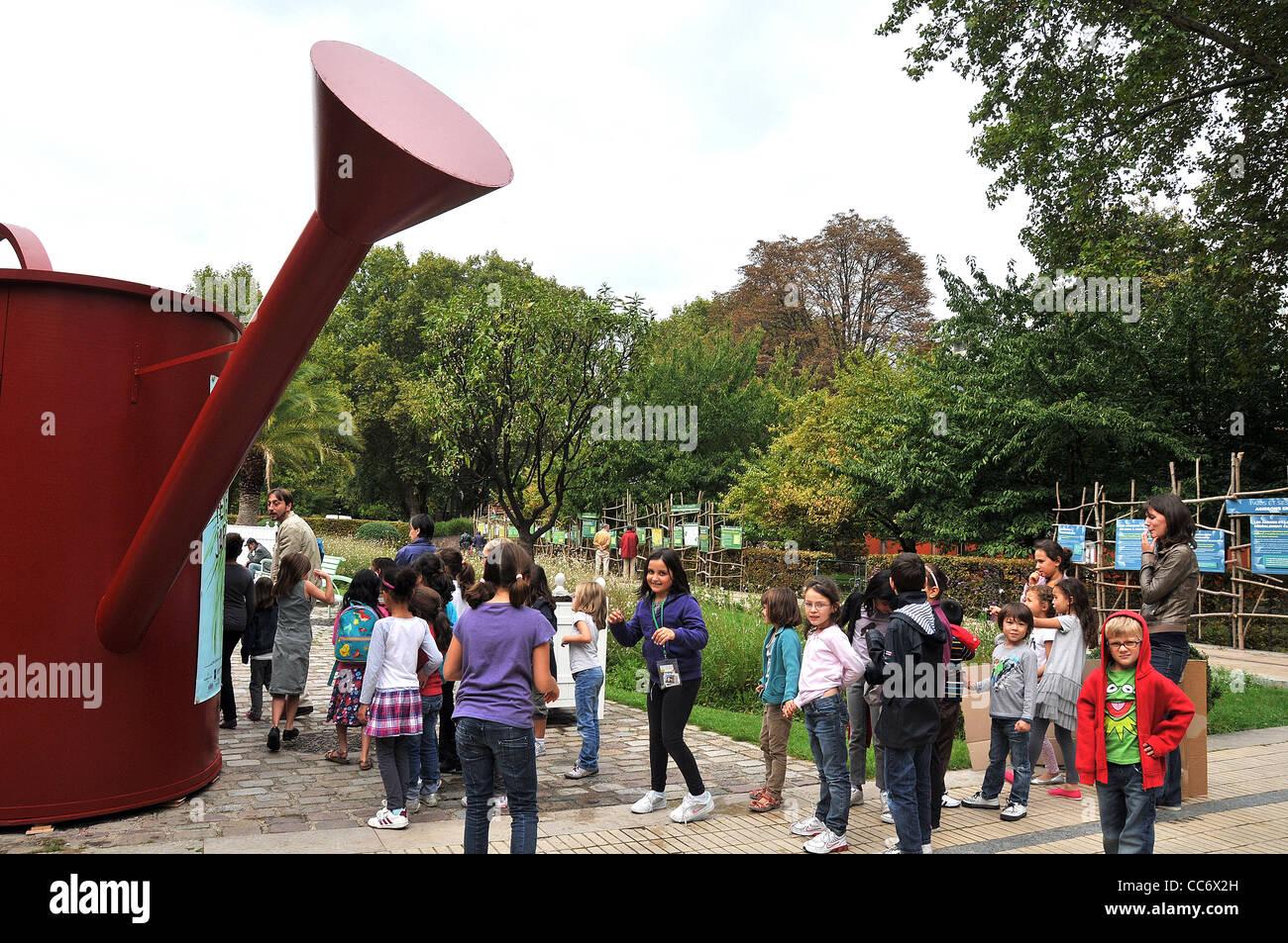 schoolchildren before giant watering can visiting Bercy garden Paris France - Stock Image
