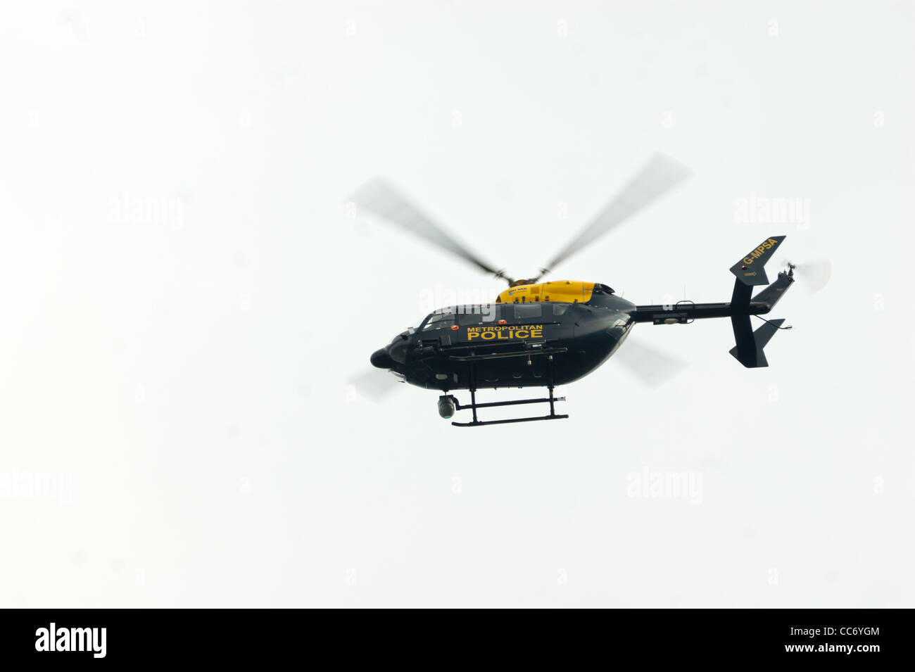 Metropolitan police helicopter flying low,  searching for  elusive quarry in North London, England UK  summer 2011. - Stock Image