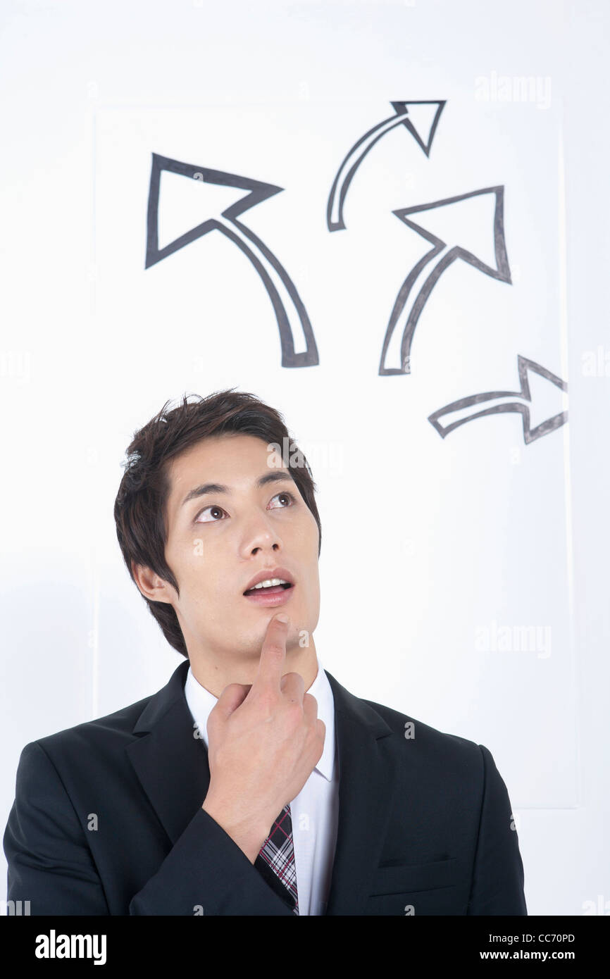 A thinking man having a finger on his chin with rising arrows - Stock Image