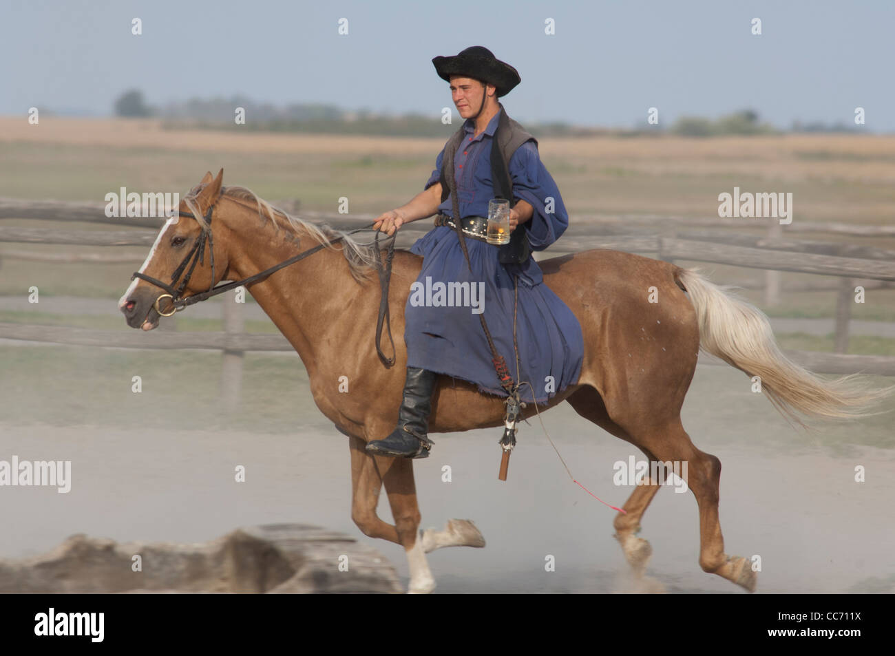 Hungary, Kalocsa. Traditional Hungarian ranch & cowboy show. Typical cowboy with beer mug on palomino horse. Stock Photo