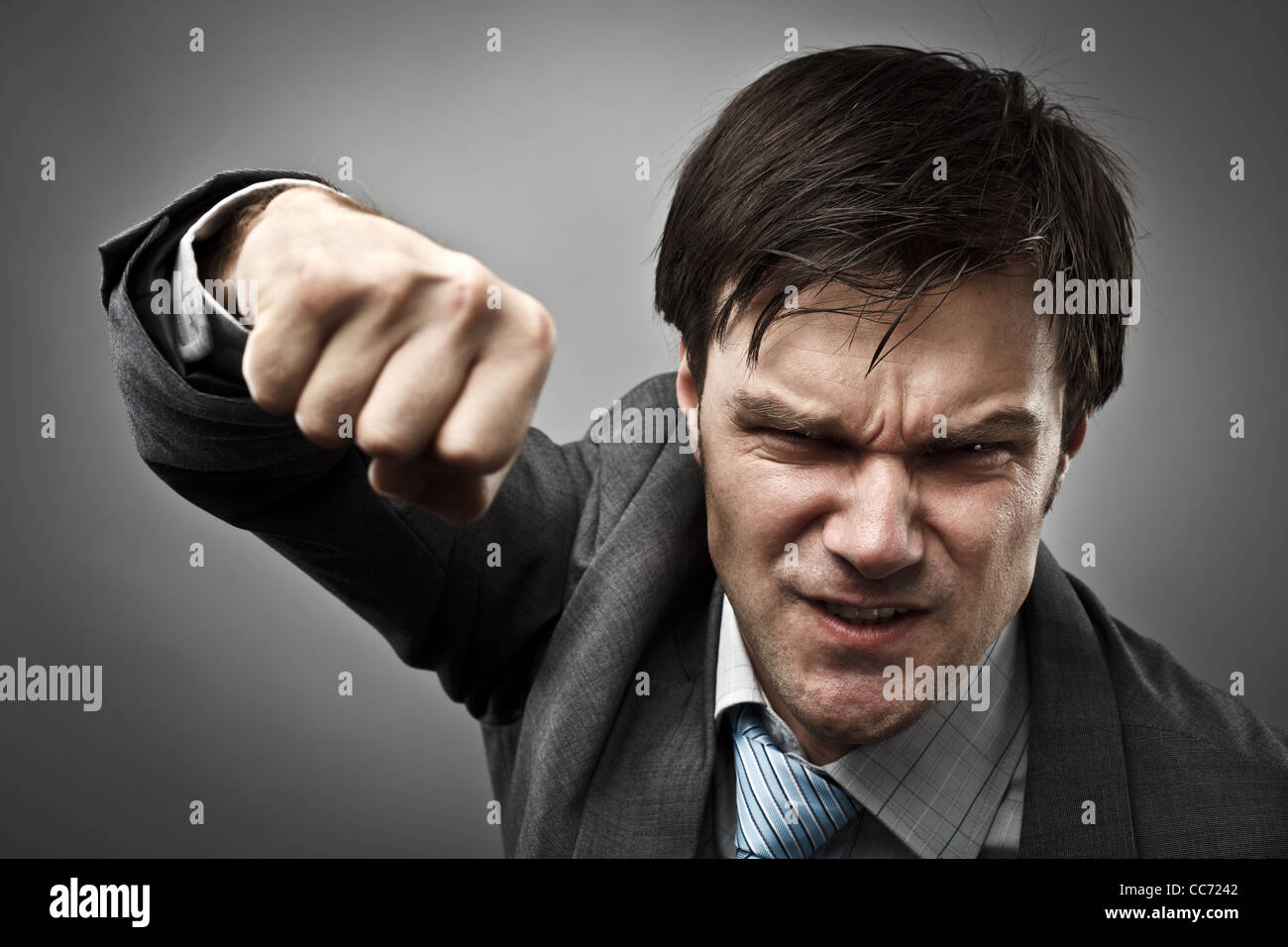 Studio portrait of an aggressive businessman punching - Stock Image