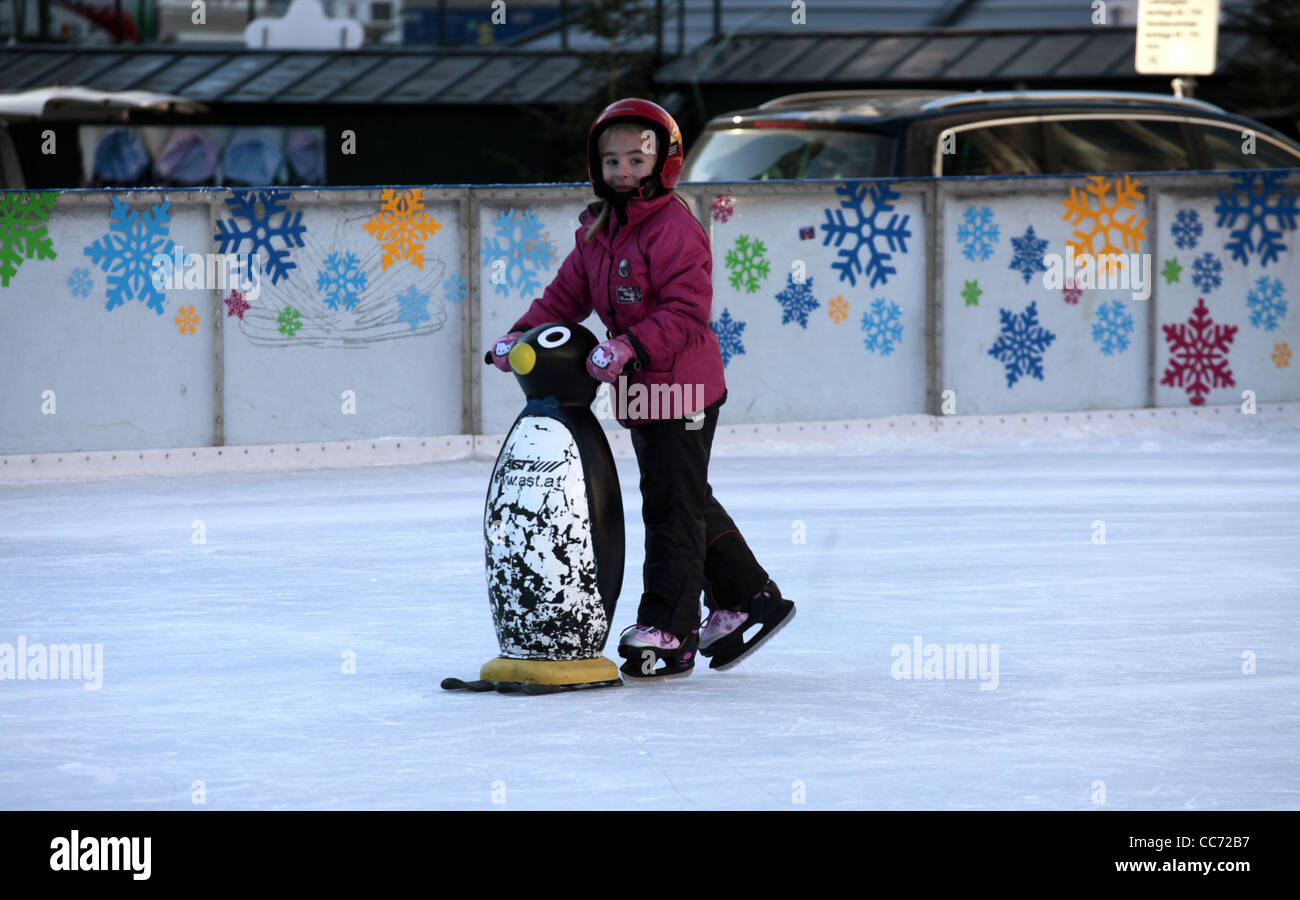GIRL LEARNS TO ICE SKATE WITH PENGUIN SALZBURG AUSTRIA 27 December 2011 - Stock Image