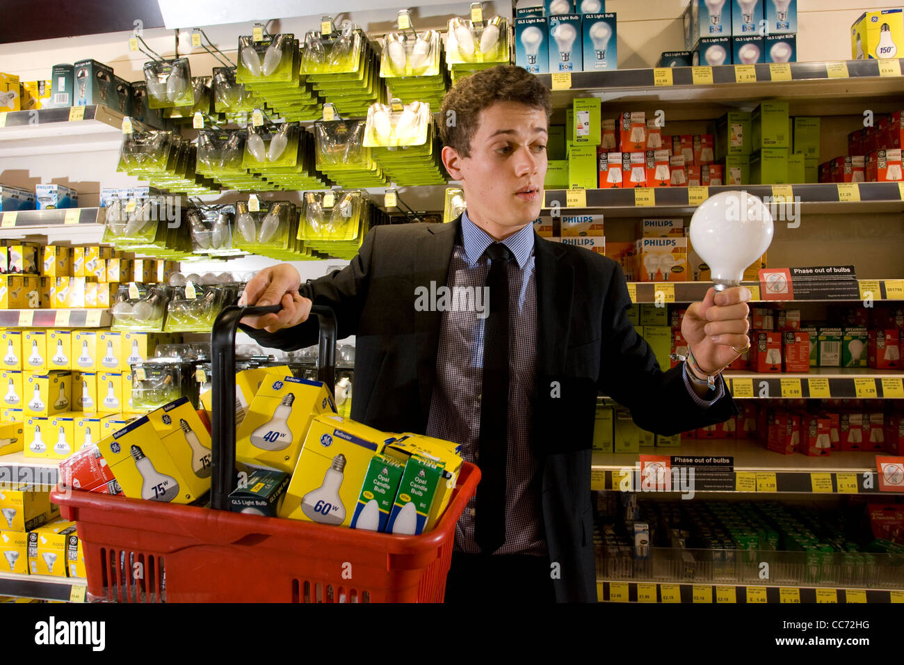 Man Contemplates Which Type Of Light Bulb To Buy In Electrical Shop As  Energy Inefficient