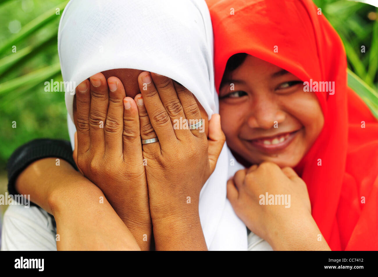 Indonesia, Sumatra, Banda Aceh, two shy girl friends with veils, hiding in front of camera Stock Photo