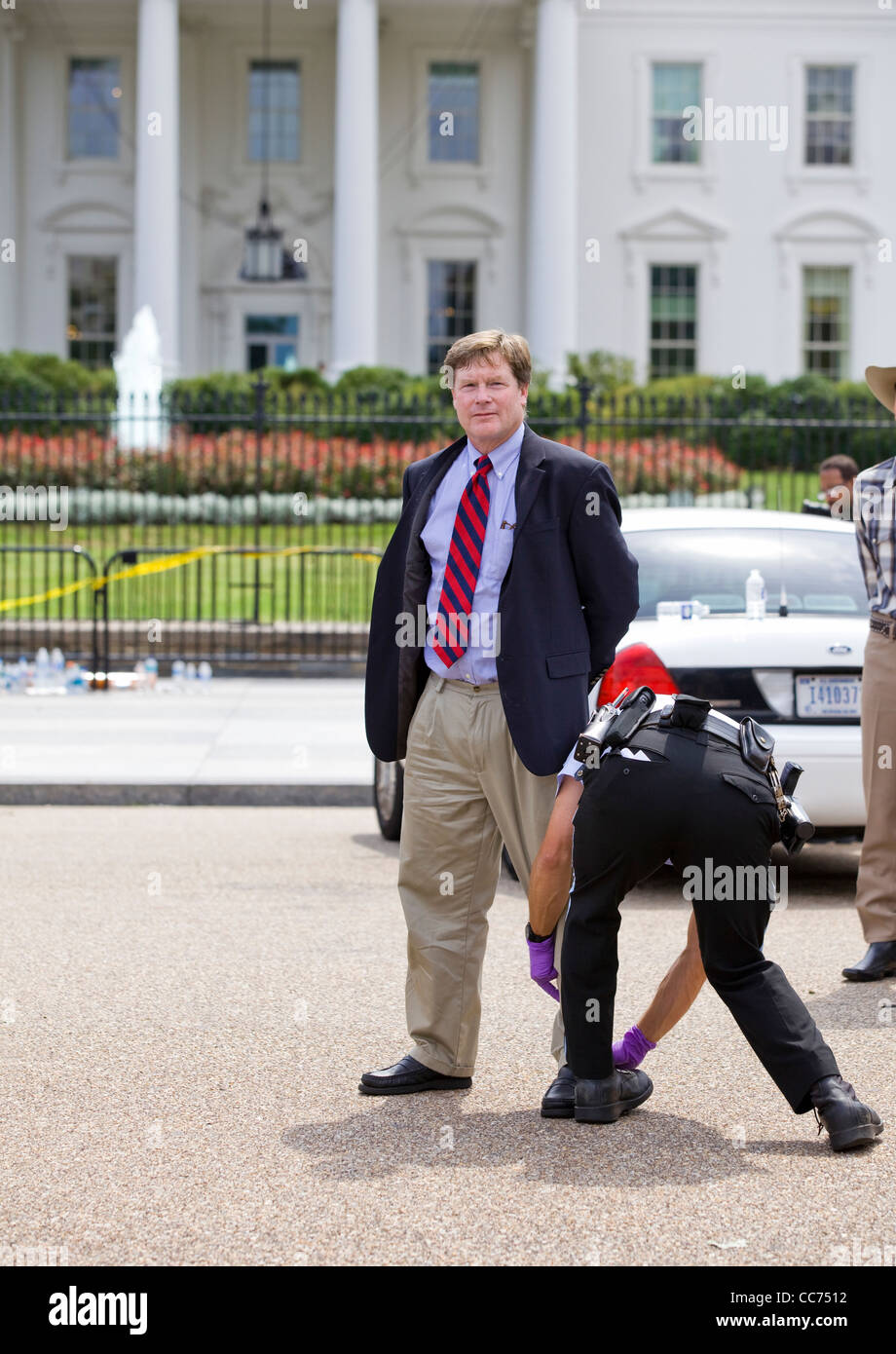 Detained demonstrator getting frisked for processing in front of the White House - Stock Image