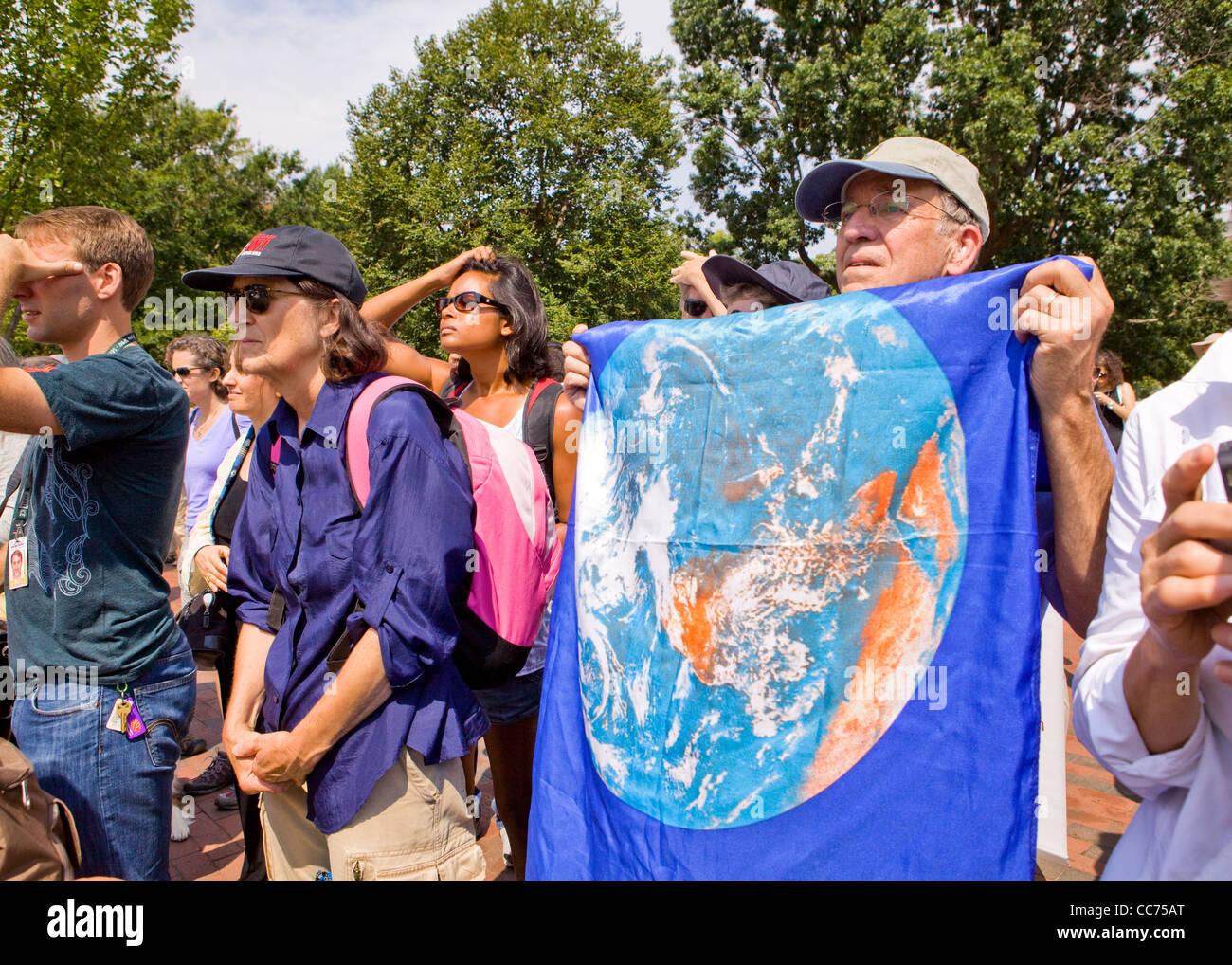 An elderly demonstrator holding up an earth flag - Stock Image