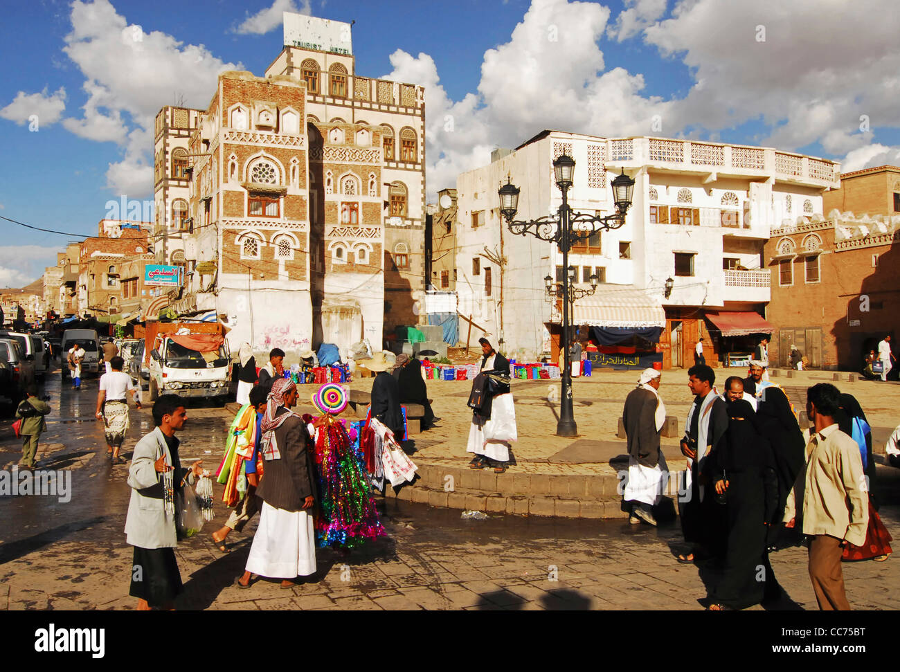 Yemen, Sanaa, busy market street with hawker holding articles for sale, group of people walking on street - Stock Image