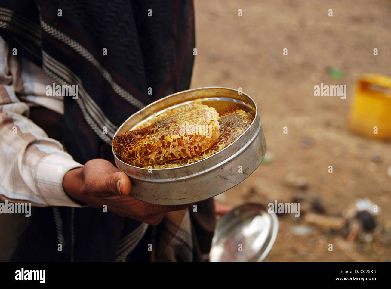 Yemen, Inland, close-up midsection of a man holding honeycomb inside a container - Stock Image