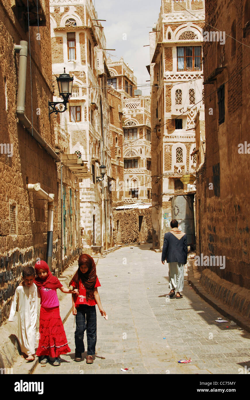 Yemen, Sanaa, three small children walking along narrow lane amid old buildings - Stock Image