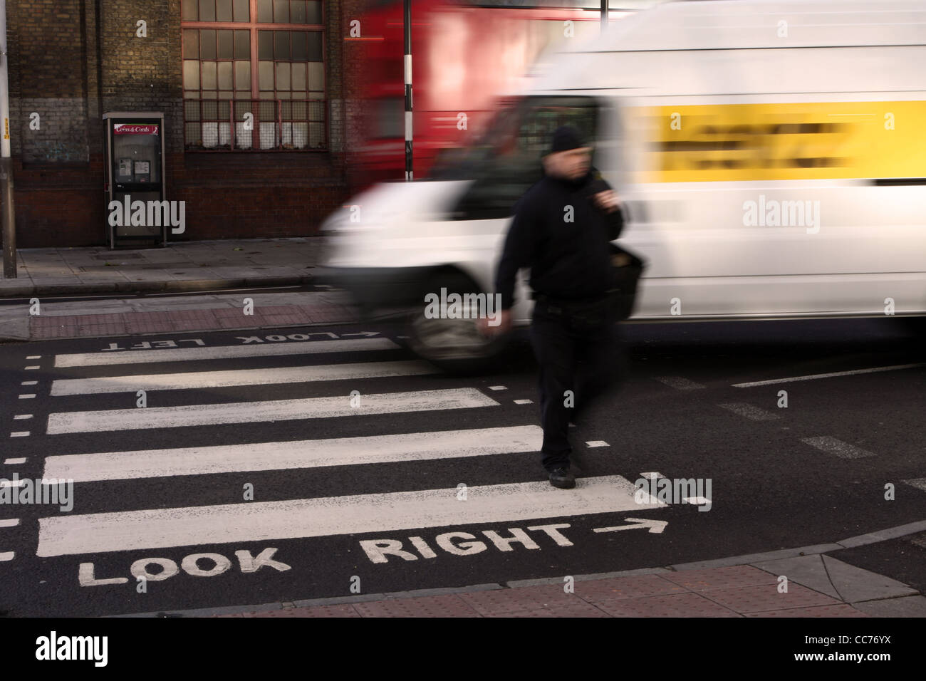 a blurred figure of a man walks across a zebra crossing in London while a van passes behind Stock Photo