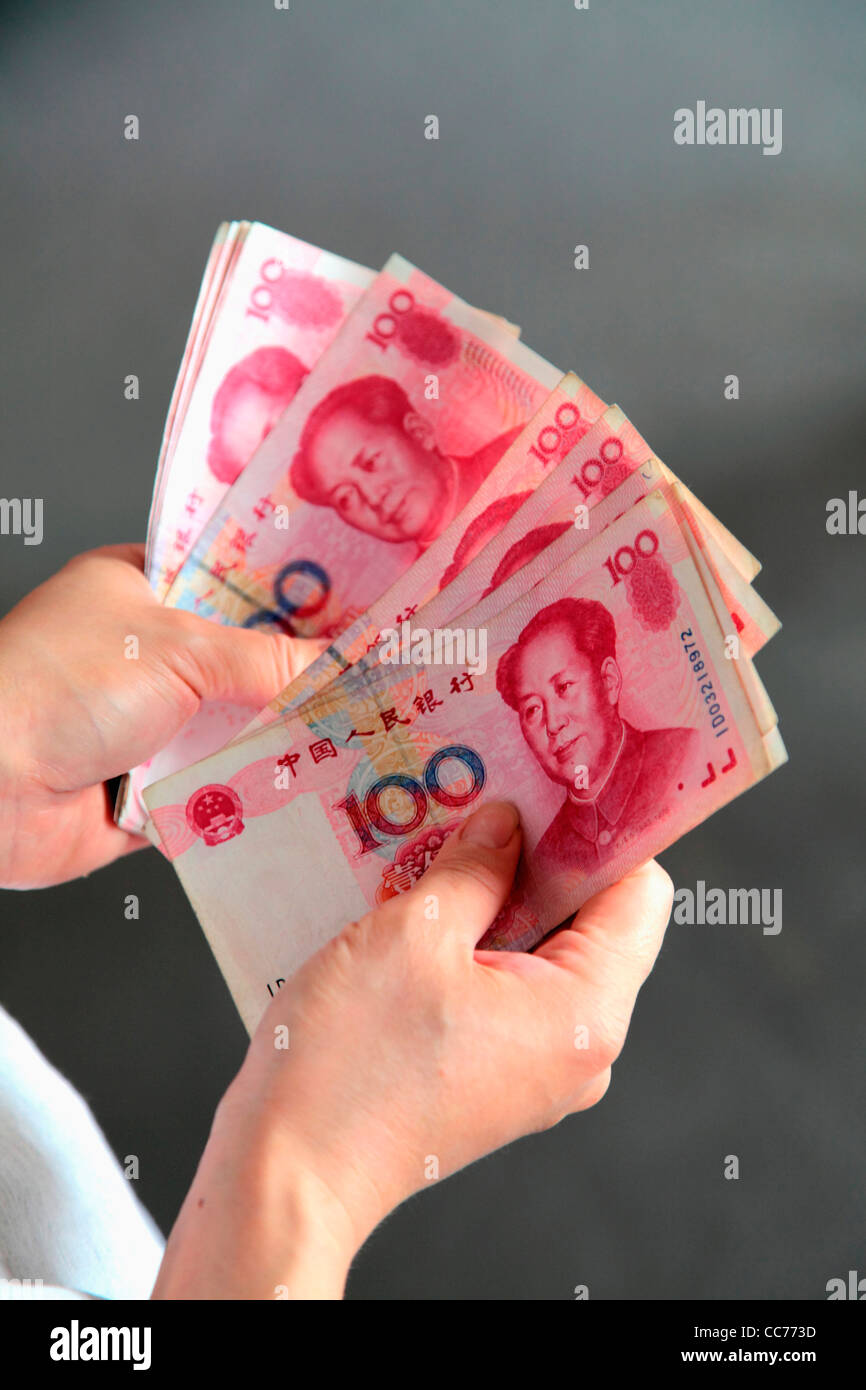 France, Paris, Hands with 100 Chinese Yuan bills - Stock Image