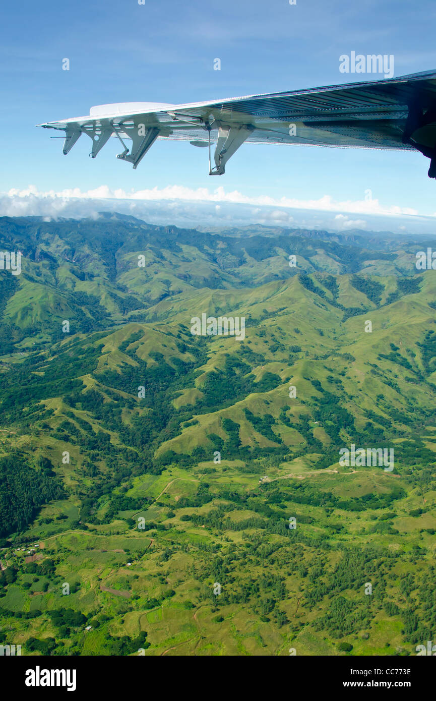 Fiji above aerial airplane wing flying over green mountains - Stock Image