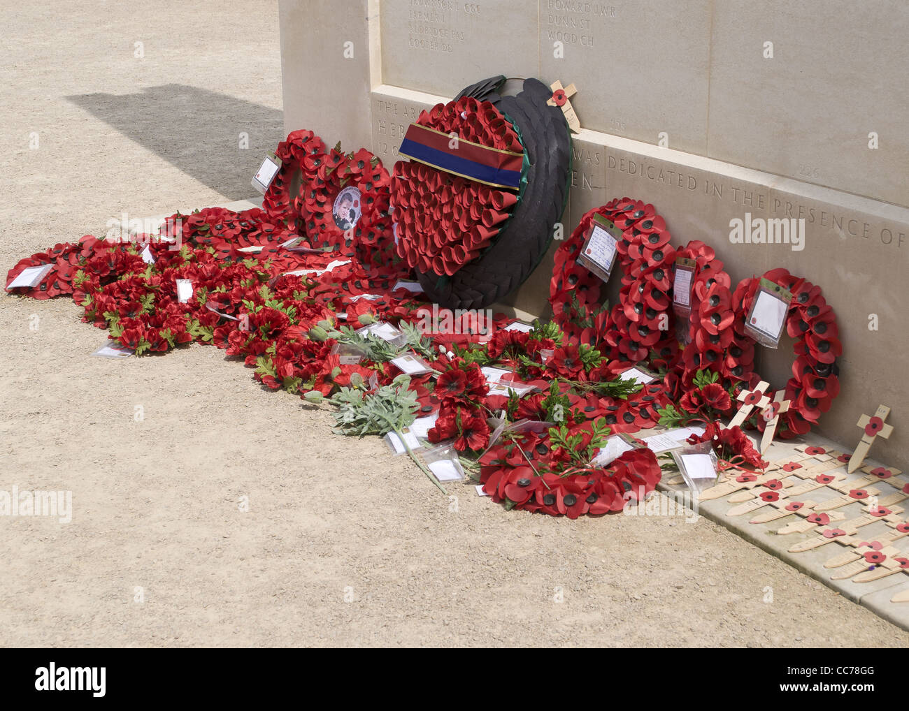 Poppy reefs layed at the base of a war memorial - Stock Image
