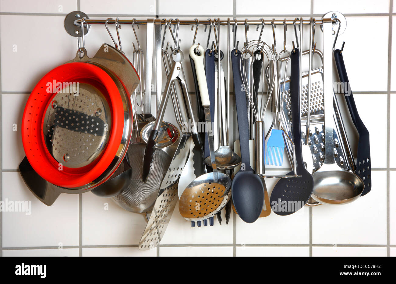 Various kitchen utensils, kitchen tools, hanging at a kitchen wall rack. - Stock Image