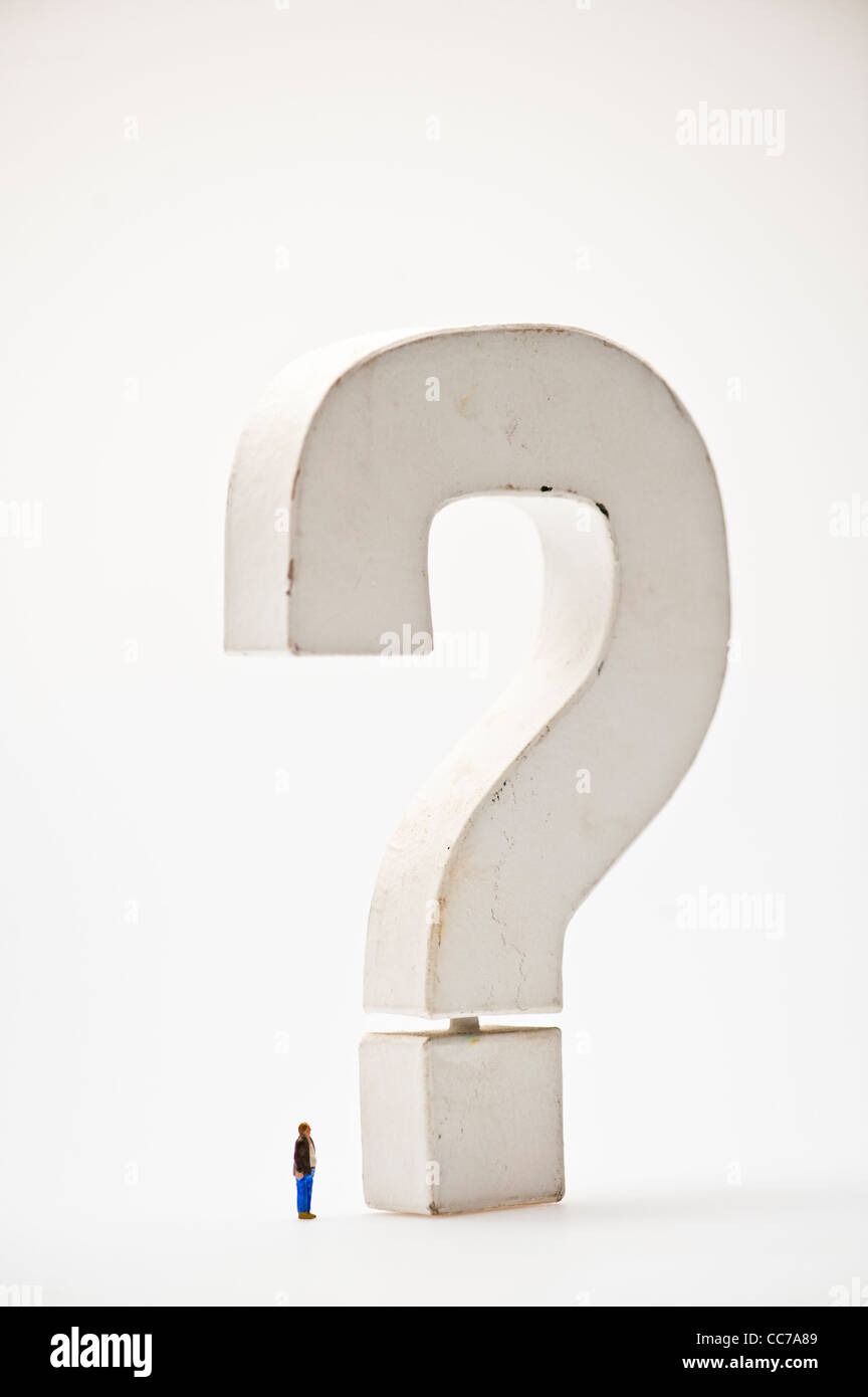 the big question - small figure dominated by a big large huge monumental question mark - Stock Image