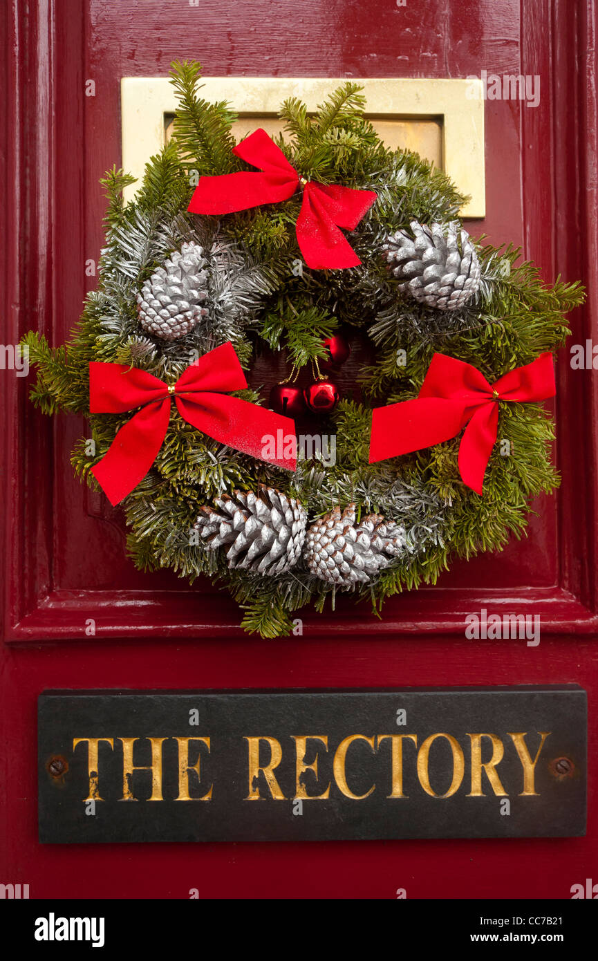 a traditional Christmas wreath on the door of The Rectory house home UK - Stock Image