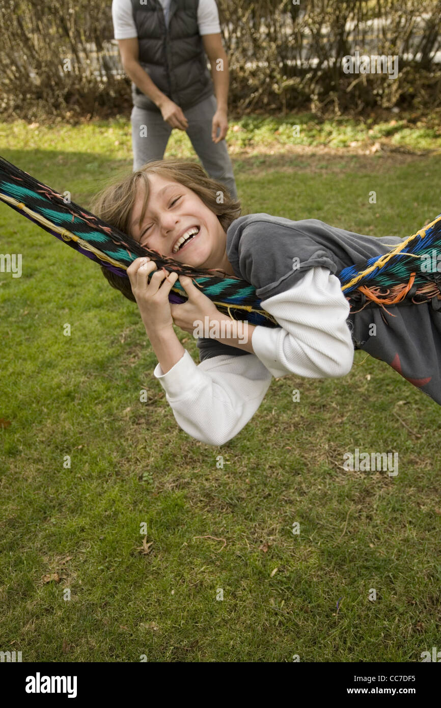 Seven year old boy being swung on the family hammock by dad in the background. - Stock Image