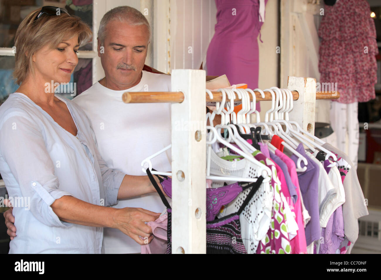 Couple shopping for women's clothes - Stock Image