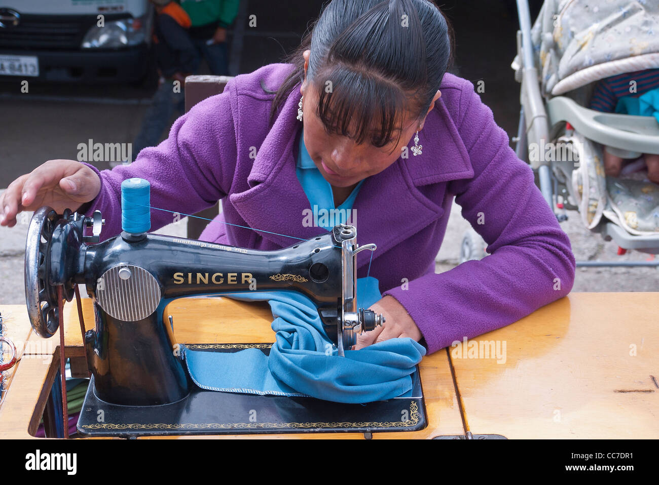 A teenager sews on her old style Singer sewing machine in the outdoor market in Saquisili, Ecuador. - Stock Image