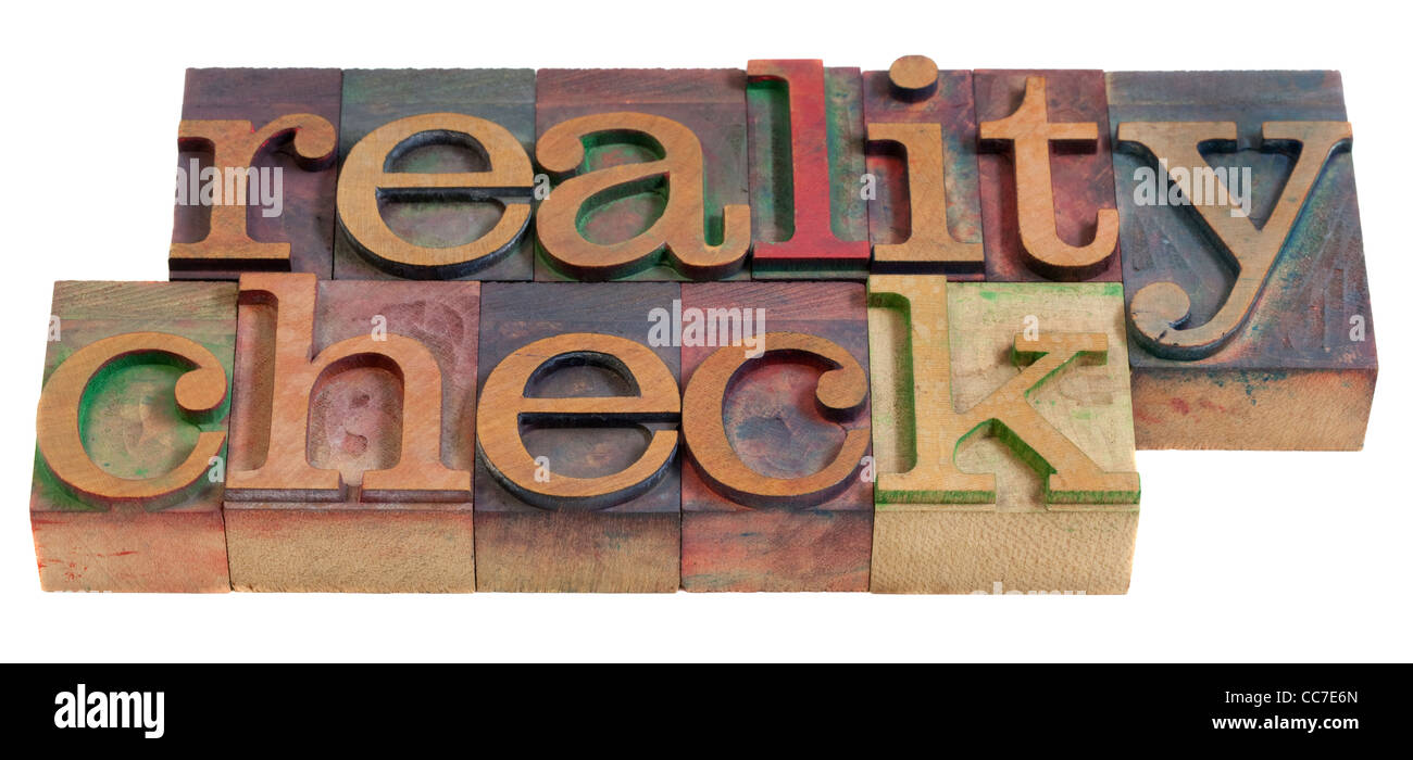 reality check concept - words in vintage wooden letterpress printing blocks, stained by color inks, isolated on - Stock Image